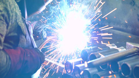 Welder in a protective mask welds parts in a metalworking plant Live Action
