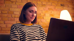 Closeup portrait of young pretty female studying online the laptop sitting on Footage