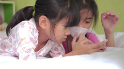 Asian children's little girls using smart phone lying in bed in a bedroom Footage