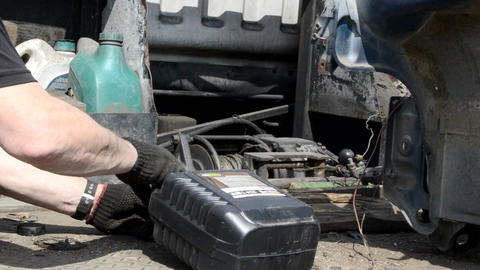 A mechanic pours automobile oil into a tow truck Live Action