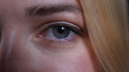 Closeup half face shoot of young pretty blonde caucasian female with blue eyes Footage