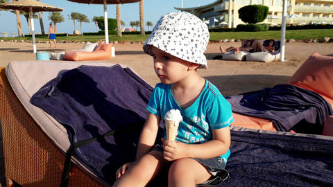 4k footage of cute little boy sitting on the sunbed and eating icecream Archivo