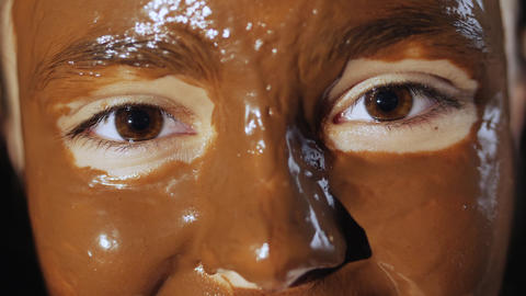 Face of a young girl with a chocolate facial mask Live Action