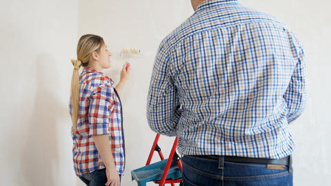 Video of happy young couple painting walls with paint roller in their new Archivo