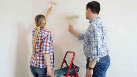 [alt video] Video of happy young couple painting walls with paint...