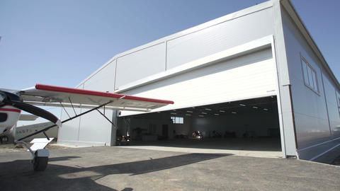 Small airplanes outside hangar. Door is opening. Visible... Stock Video Footage