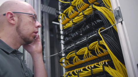 it guy checks server rack talking on the phone Live Action