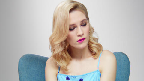 [alt video] blond woman with stylish makeup sits in cozy armchair