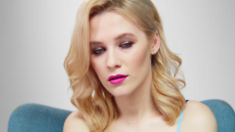 blond woman with stylish makeup sits in cozy armchair Footage