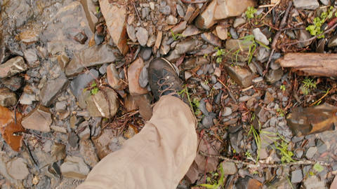 Pov view of the legs with hicking shoes of the man that walking on stones GIF