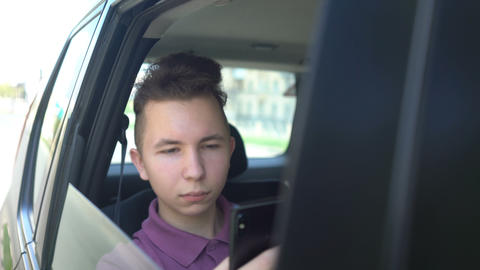 teenager using app on his phone on sunny day in backseat… Stock Video Footage