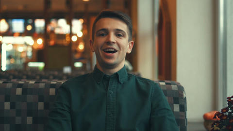 Happy attractive young man looking at the camera and smiling in a cafe Footage