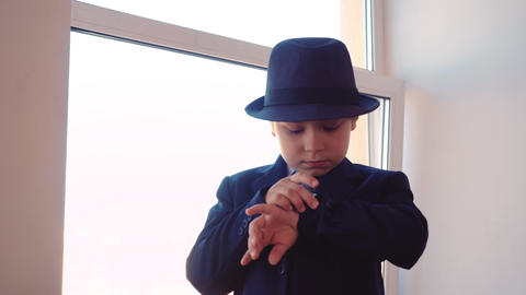 Serious young boy in business suit and hat looking wrist watch on window Footage