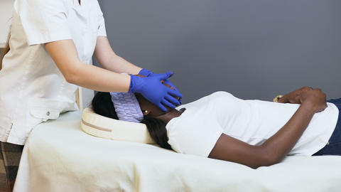 Female cosmetologist making relaxing massage to the female african client Footage