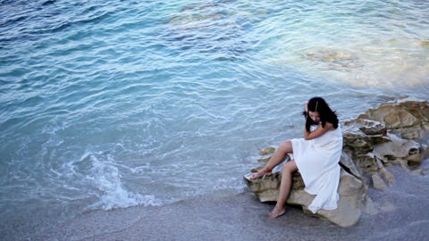 Beautiful girl in white dress is sitting on the beach. Greece GIF