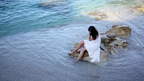 [alt video] Beautiful girl in white dress is sitting on the beach....
