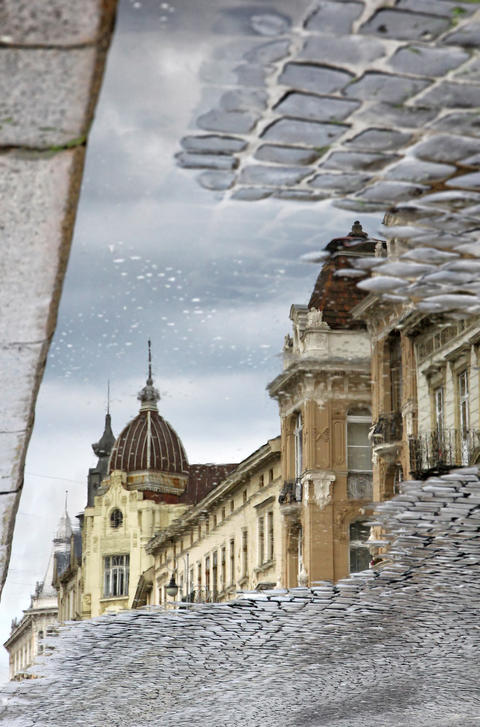 Buildings at the street reflecting in a puddle after rain Fotografía