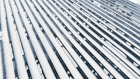 AERIAL: Photovoltaic in winter covered with snow. Solar panels among the snow Live Action