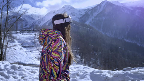 Beautiful young girl wearing ski goggles. Smiles and gets pleasure from the Footage