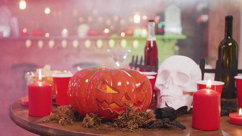 Carved pumpkin as a halloween still life and other decor elements in a bar Footage