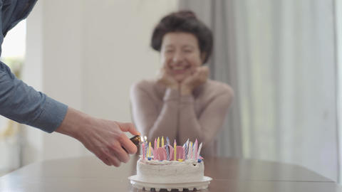 The blurred figure of the positive smiling lady sitting at the table on the Footage