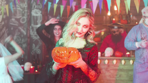 Sexy vampiress with a jack-o-lantern in her hands at a halloween party Footage