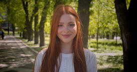 Portrait of cute ginger girl turns to camera smiling being happy into camera in Footage