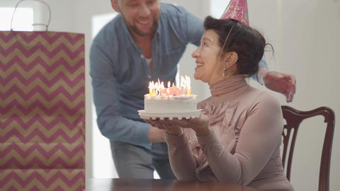 Portrait emotional smiling lady sitting at the table holding the small cake with Footage