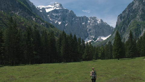 Aerial - Young woman hiking through a grass field to the mountain Footage