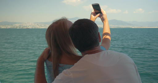 Couple enjoying sea travel and taking selfie Live Action