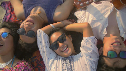 Fun attractive young people laying on the beach over head crane shot Footage