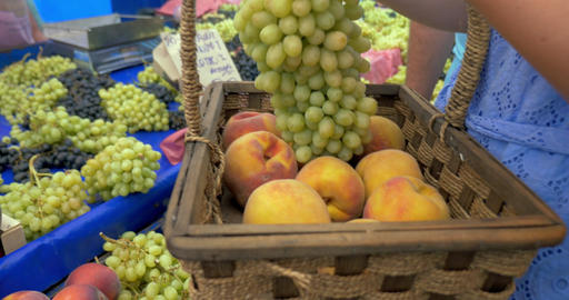 Woman buying grapes and peaches on market Footage