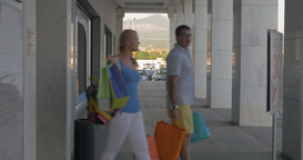 Couple with bags leaving shopping centre Footage