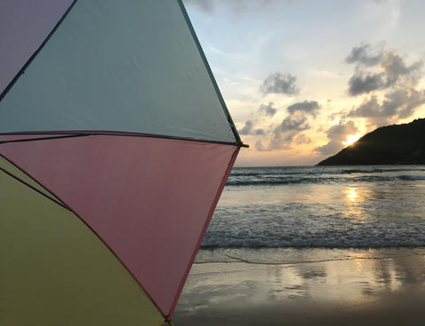 sunset on beach with pastel colorful umbrella and beautiful sunlight Photo