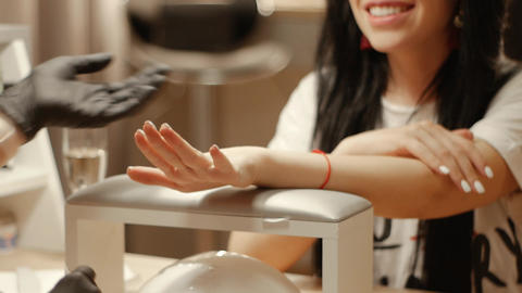Manicurist examines client's nails Live Action