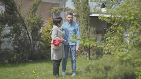 Mature woman with the basket with tulips in hands talking with her grandson on Footage