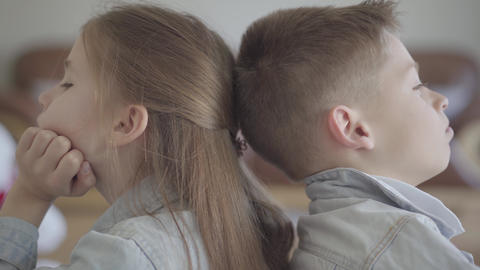 Close up portrait twin boy and girl sit on the floor of living room back to back Live Action