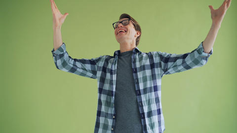Excited guy looking at camera laughing and raising arms on green background Live Action