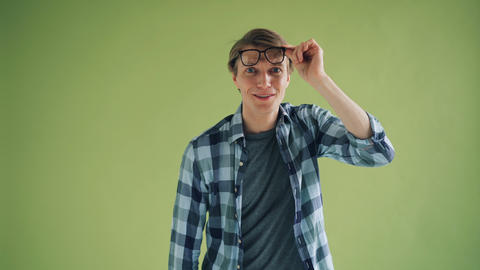 Portrait of astonished young man raising glasses looking at camera and smiling Live Action