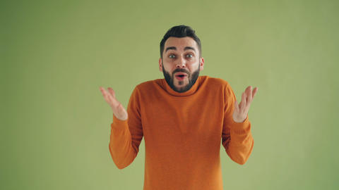 Portrait of excited hipster guy rejoicing raising arms fists and screaming yes Live Action