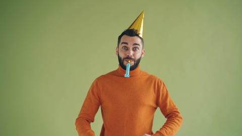 Playful young man wearing birthday hat blowing party horn having fun Footage