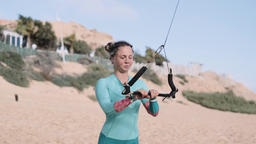 Female Kiteboarder Stretching and Warming Up on Beach Archivo