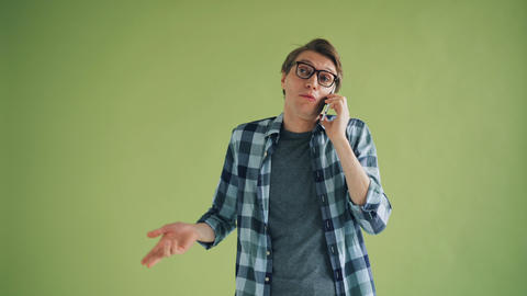 Cheerful young man talking on mobile phone and gesturing on green background Footage