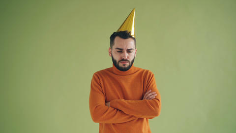 Portrait of upset man in party hat standing alone with arms crossed sighing Footage
