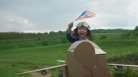 Little boy waving a flag of america outdoors Footage