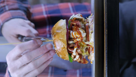 A waiter or cook cuts a huge burger into two halves. Street food, unhealthy junk Footage