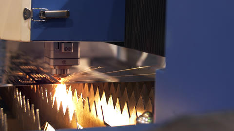 Industrial laser cutter with sparks. The programmed robot head cuts with the aid Live Action