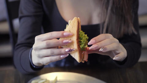 Sexy young girl eats sedvich. Close-up. The concept of quick snack and obesity Footage