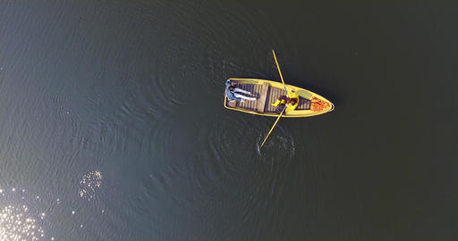Two people in the small boat boating across a beautiful wide reflective lake or Footage