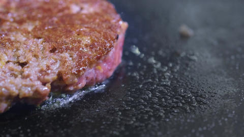 Cooking a hamburger, patty or steak. On a hot stove, a cook fries meat in a Footage
